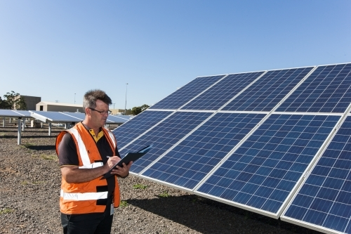 employee taking notes at a solar panel plant