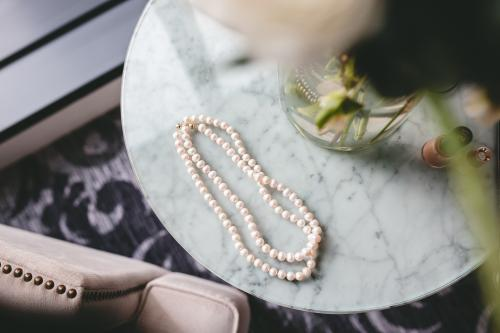 Pearl necklace on marble coffee table