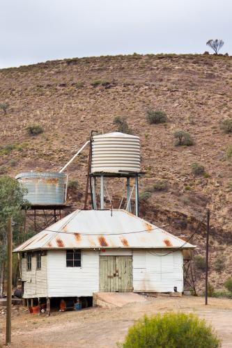 A tin shed and rainwater tanks at the base of a hill in the outback