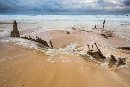 Waves recede over scrap metal pieces of a shipwreck on a beach