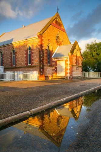 An historic brick church reflected in roadside puddles