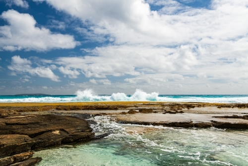 Spectacular view of water flowing into rock pools with surf crashing behind and dramatic sky