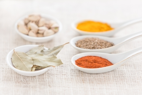 spices, nuts and bay leaves in white spoons on white cloth
