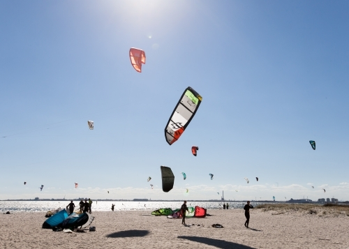 People kitesurfing at a city beach