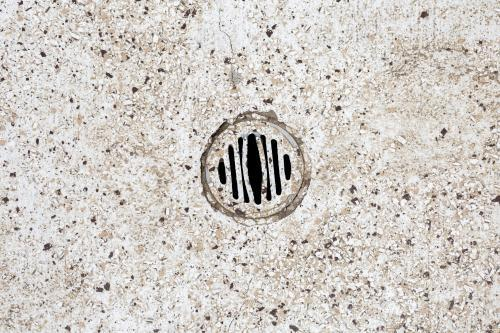 Stone floor with water drain in public toilets