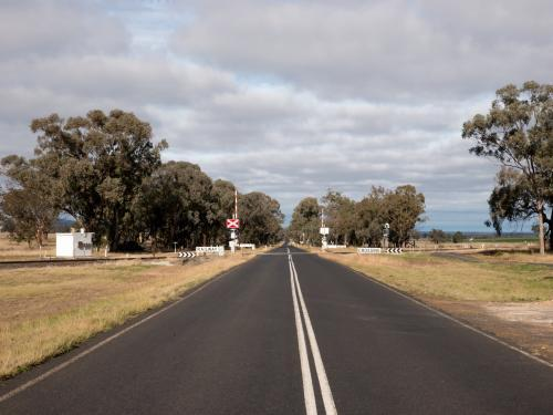 Straight bitumen road with double white lines and level crossing