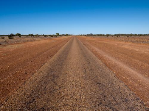 Straight single laned sealed road disappearing in the distance