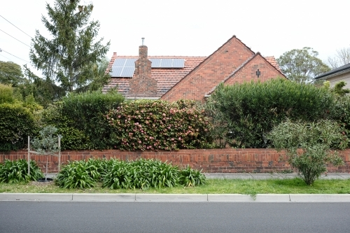 Street view of an old brick house surrounded by garden