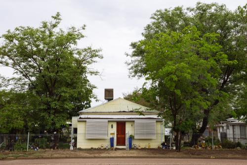 Street view of an old yellow weatherboard house in an outback town