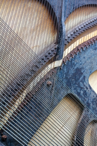 Strings crossing on back of piano