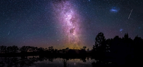 Stunning view of purple milky way over trees and lake