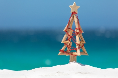 Summer sun shines down on a driftwood Christmas tree decorated with a string of red baubles