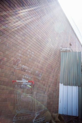 Sun rays on a lost shopping trolley in an alleyway