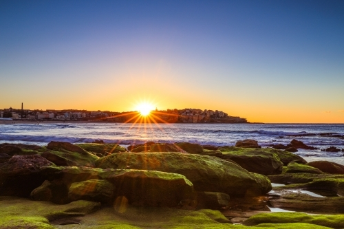 Sun rising over moss covered rocks along coastline with blue sky