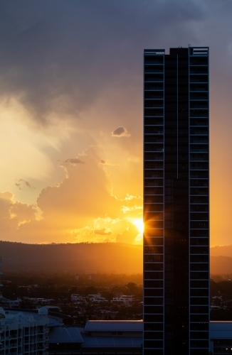 sun setting behind high rise building