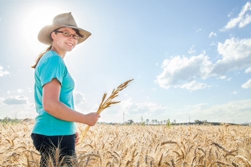 Sunflare behind a happy farm girl holding a sheaf of bearded wheat