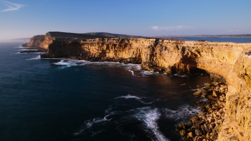 Sunlit cliffs surrounded by ocean
