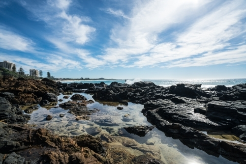 Sunlit rock pools along the coast at Coolum
