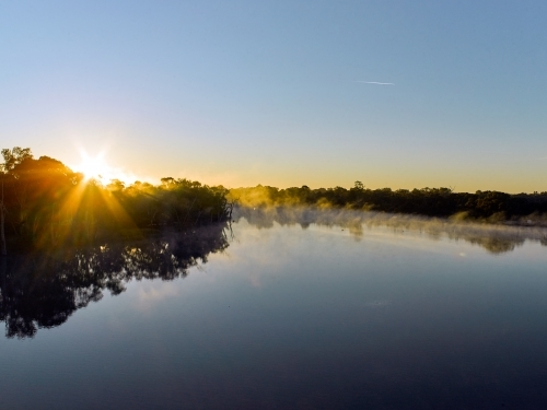 Sunrise and mist on a river in the country