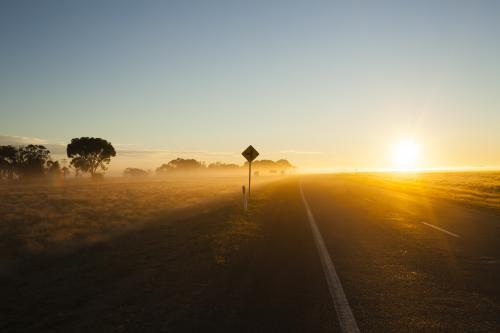 Sunrise on a  regional highway with silhouette road side sign