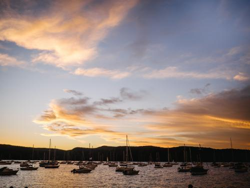 Sunset over boats on harbour with mountains behind