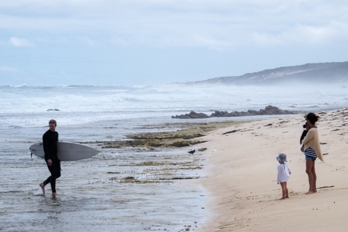 Surfer exiting ocean with young family waiting on the rugged remote beach shoreline