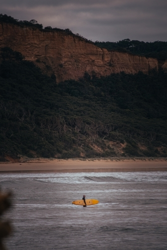 Surfer Standing on a Sand Bank in front of a Great Ocean Road Cliff