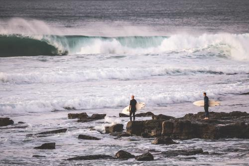 surfers getting ready to enter the ocean from rocks