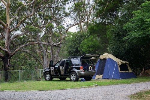 SUV and tent set up on campsite overlooking beautiful bushland