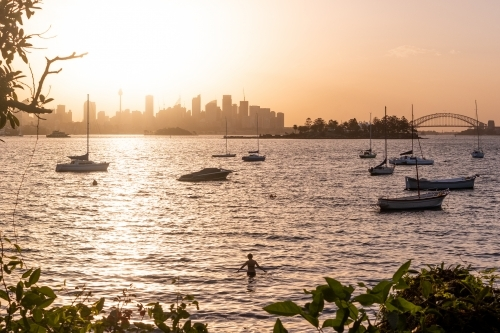 Swimmer enjoys the sunset over Sydney city