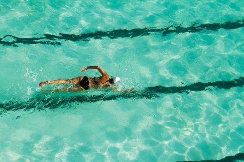 Girl swimming laps in a pool overhead view