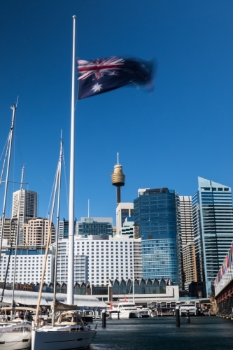 Sydney skyline from Darling harbour with Australian Flag flown half mast