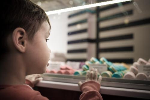 Cute 4 year old mixed race boy chooses a macaron treat