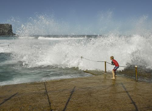 Boy hanging onto railing at rockpool with breaking wave