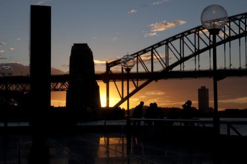 Sun setting behind the south pylon of the Sydney Harbour Bridge