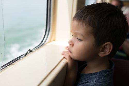 Cute 3 year old mixed race boy looks out a boat window