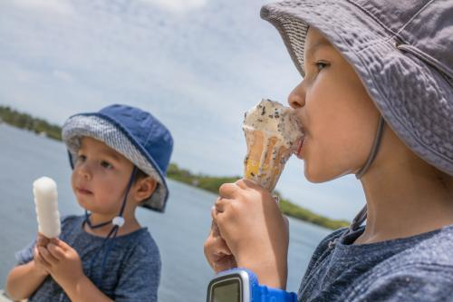 3 and 5 year old mixed race boys eating ice-cream on a warm summer day