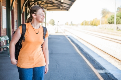 Teen girl in orange shirt with bag waiting at train station