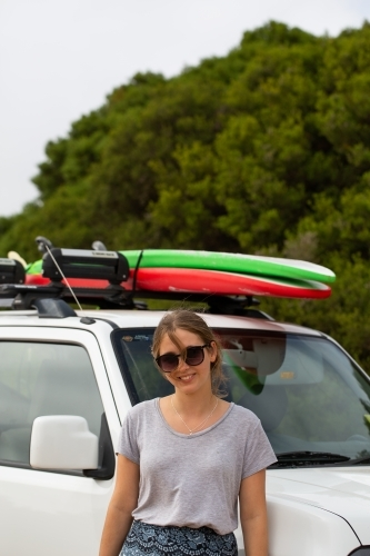 Teen Girl Leaning Against Suv With Surfboards On Roof Rack