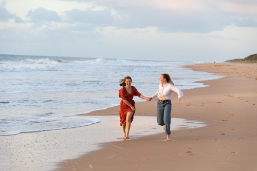 teen girls running on beach hand in hand
