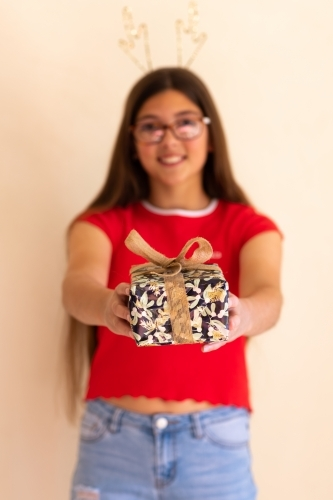 teen with long hair and glasses holding out gift-wrapped box
