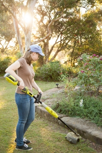 Teen girl cutting grass with whipper snipper in golden afternoon light