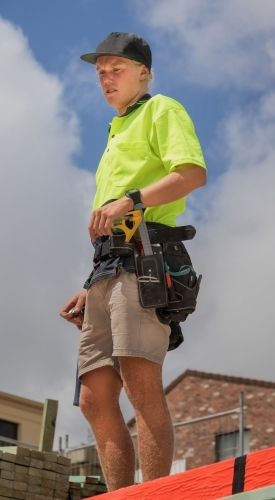 Teenage apprentice builder with tool belt on residential construction site