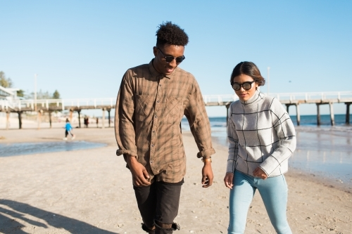 Teenage boy and girl walking on the beach