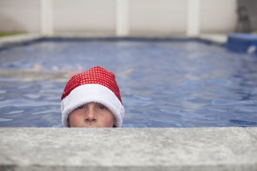 Teenage boy in Santa hat celebrating christmas in a pool