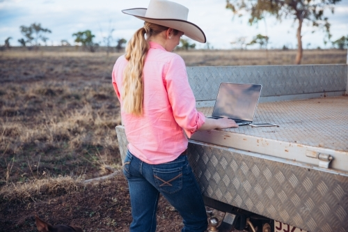 Teenage Female farmer using laptop in the paddock