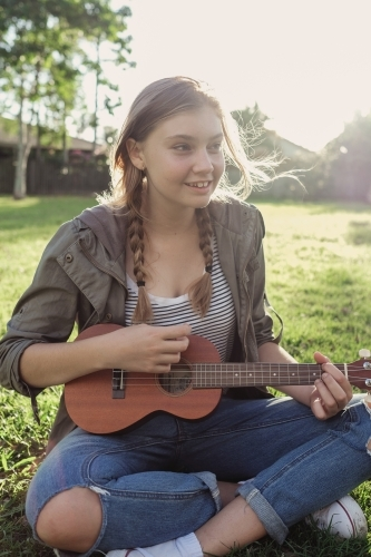 Teenage girl playing ukulele in the park
