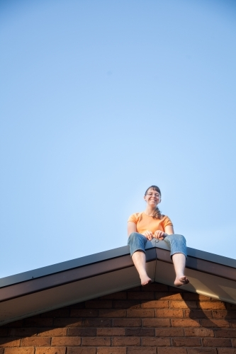 Teenage girl sitting on the house roof grinning