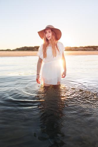 Teenage girl standing in calm water at the beach at sunset