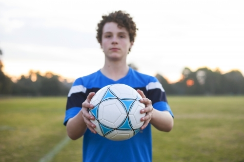 Teenage soccer player on a soccer pitch with ball